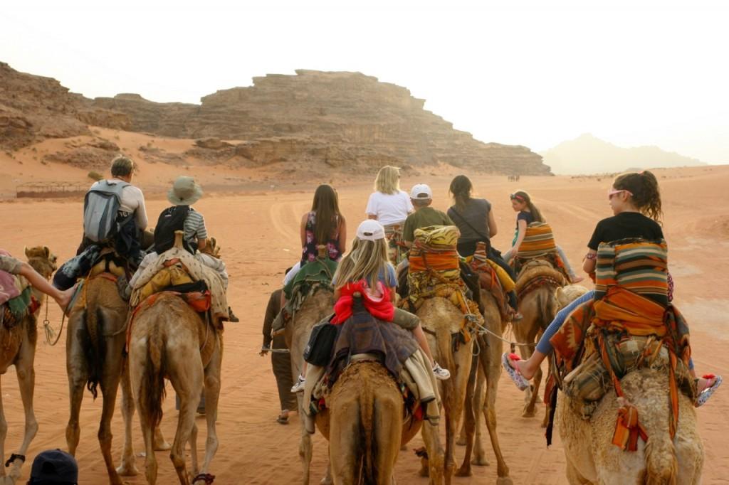 Flea riding a camel on a press trip to Jordan